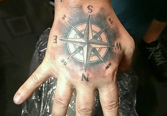 Black and grey compass tattoo on the hand