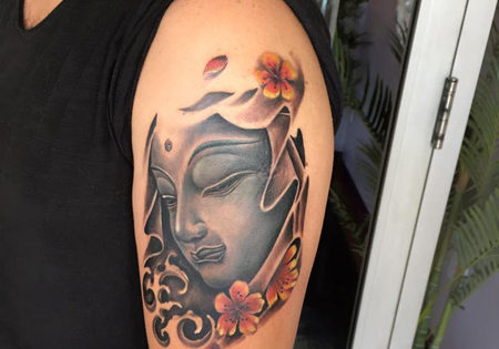 Colorful Buddha Tattoo on the upper arm