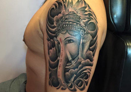 Black and grey tattoo of Ganesha on the upper arm done by Ozmany ponce